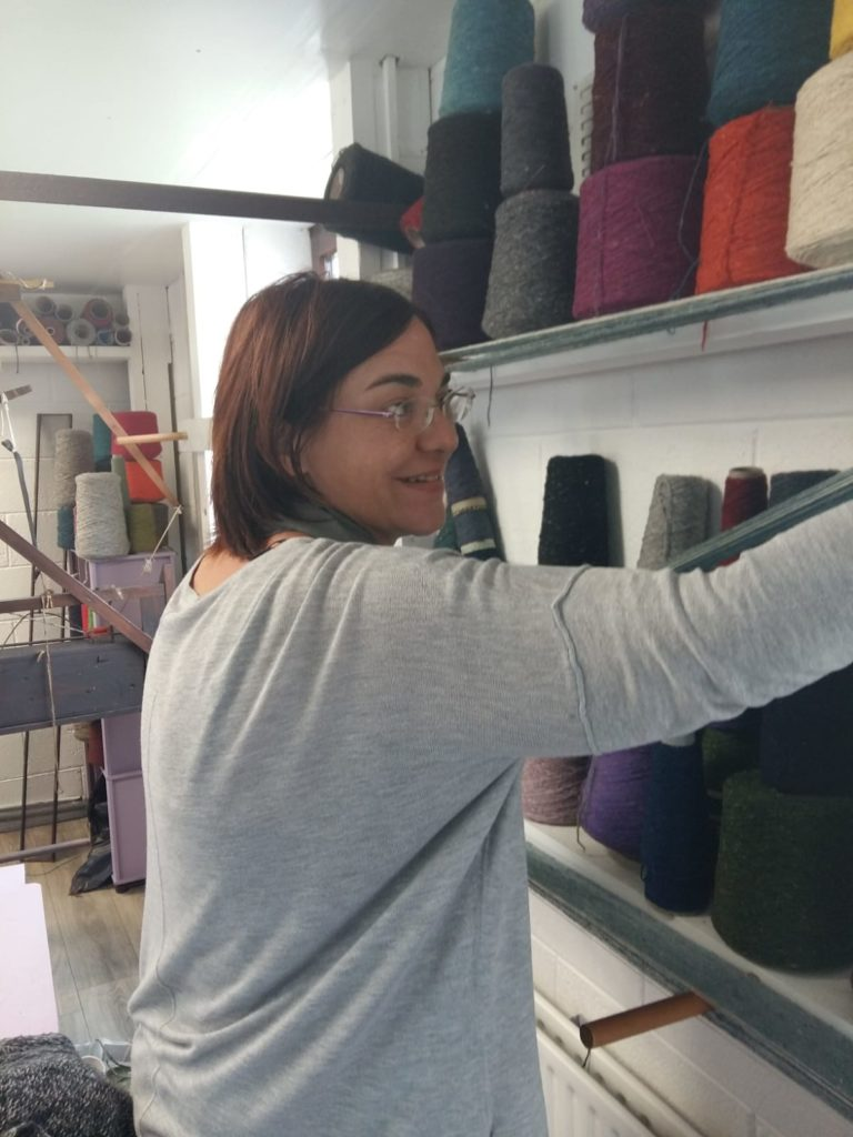 Picture of me making a warp wrapping yarn around pegs on the wall of my studio