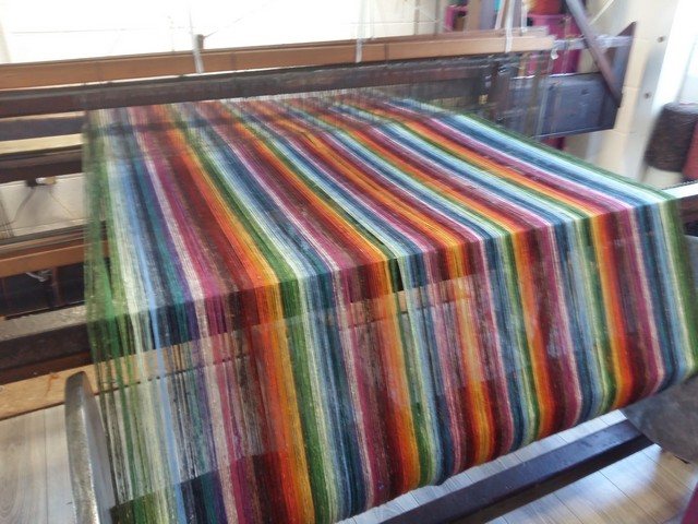 A picture of my 120 year old loom with a colourful commission warp on it